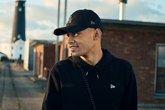 Abbildung eines Mannes, der eine schwarze Baseballkappe von New Era mit Camouflage-Infill-Logo trägt
