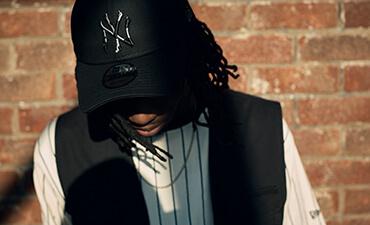 Abbildung eines Mannes, der eine schwarz 9FORTY-Kappe von New Era trägt