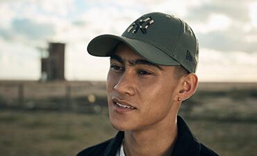 Abbildung eines Mannes, der eine olivgrüne Baseballkappe mit Camouflage-Infill-Logo der New York Yankees trägt
